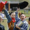Sam Walter, left, and classmate Trevor Buckner wave their hats and shout at