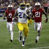 Photo - LSU running back Kenny Hilliard (27) rushes for a touchdown as Wisconsin cornerback Peniel Jean (21) and cornerback Sojourn Shelton (8) pursue during the second half of an NCAA college football game Saturday, Aug. 30, 2014, in Houston. LSU won 28-24. (AP Photo/David J. Phillip)