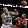 Photo - San Antonio Spurs shooting guard Manu Ginobili, left, of Argentina, defends against Toronto Raptors forward Patrick Patterson during the first half of an NBA basketball game on Monday, Dec. 23, 2013, in San Antonio. (AP Photo/Darren Abate)
