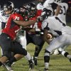 Hartsville defenders Dwayne McDaniel (78) and Ronald Rouse (74) tackle Crestwood running back Rakeen Benjamin during the first quarter of Friday\'s game in Hartsville. Rouse collapsed during the second quarter of the game and later died at a local hospital. The game was suspended at halftime. (AP Photo/Bob Sloan, Florence Morning News)