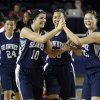 CLASS 5A GIRLS HIGH SCHOOL BASKETBALL: Shawnee\'s Taylor Cooper (foreground left) and Micaela Yu (right) high five as they walk off the court with teammates Kelsee Grovey (center) and Bailey Taylor (background left) after their win over Carl Albert during a basketball game at Oral Roberts University in Tulsa on Friday, March 9, 2012. MATT BARNARD/Tulsa World