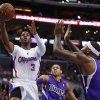 Photo - Los Angeles Clippers guard Chris Paul shoots the ball in front of Sacramento Kings guard Ray McCallum, center, and Kings center DeMarcus Cousins, right, during the first half of an NBA basketball game in Los Angeles, Sunday, April 12, 2014. (AP Photo/Danny Moloshok)