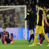 Photo - Barcelona's Gerard Pique, left sits on the pitch after getting injured during a first leg quarterfinal Champions League soccer match between Barcelona and Atletico Madrid at the Camp Nou stadium in Barcelona, Spain, Tuesday April 1, 2014. (AP Photo/Manu Fernandez)