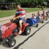 Cavett Lee drives a riding lawn mower as it pulls, from front to back, Claire Duginski, 5, Hannah Lee, 6, Grace Duginski, 10, Samuel Duginski, 9, Kolby Lee, 2, and Killian Lee, 8, during the Quail Creek Fourth of July parade along Quail Creek Road in Oklahoma City, Saturday, July 4, 2009. Photo by Nate Billings, The Oklahoman