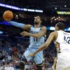 Photo - Memphis Grizzlies guard Mike Conley (11) shoots over New Orleans Pelicans center Alexis Ajinca (42) in the first half of an NBA basketball game, Wednesday, March 12, 2014, in New Orleans. (AP Photo/Scott Threlkeld)