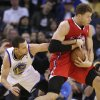 Photo - Golden State Warriors' Stephen Curry (30) reaches for the ball held by Los Angeles Clippers' Blake Griffin during the second half of an NBA basketball game in Oakland, Calif., Monday, Jan. 21, 2013. Golden State won 106-99. (AP Photo/Marcio Jose Sanchez)