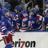 Photo - New York Rangers' Derek Stepan (21) celebrates with his teammates after scoring a goal during the first period of the NHL hockey game against the New Jersey Devils, Saturday, April 27, 2013 at Madison Square Garden in New York.  (AP Photo/Mary Altaffer)