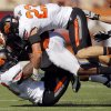 Oklahoma State\'s Zack Craig (23) and Andrae May (16) tackle Texas\' Fozzy Whittaker (2) in the first half during a college football game between the Oklahoma State University Cowboys (OSU) and the University of Texas Longhorns (UT) at Darrell K Royal-Texas Memorial Stadium in Austin, Texas, Saturday, Oct. 15, 2011. Photo by Nate Billings, The Oklahoman