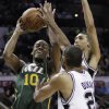 Utah Jazz\'s Alec Burks (10) works against San Antonio Spurs\' Tim Duncan, center, and Danny Green during the first quarter of Game 2 of a first-round NBA basketball playoff series, Wednesday, May 2, 2012, in San Antonio. (AP Photo/Eric Gay)