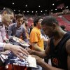 Photo - Oklahoma State guard Marcus Smart, right signs autographs during practice at the NCAA college basketball tournament Thursday, March 20, 2014, in San Diego. Oklahoma State faces Gonzaga in a second-round game on Friday. (AP Photo/Gregory Bull)