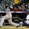 New York Yankees\' Vernon Wells, left, follows the flight of his two-run home run with Colorado Rockies catcher Wilin Rosario in the first inning of a baseball game in Denver on Wednesday, May 8, 2013. (AP Photo/David Zalubowski)
