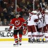 Photo - New Jersey Devils ring wing Damien Brunner (12), of the Czech Republic, skates away as members of the Phoenix Coyotes celebrate a goal by Chris Summers during the second period of an NHL hockey game, Thursday, March 27, 2014, in Newark, N.J. (AP Photo/Julio Cortez)