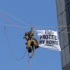 Photo - Greenpeace activists, including this one dressed in a tiger suit, rappel and hang banners in protest of Procter & Gamble outside of the company's headquarters, in downtown Cincinnati, Tuesday, March 4, 2014. The environmental organization says the 60-foot banners on P&G's two towers were in protest of the consumer products company's use of palm oil from a supplier that Greenpeace says is linked to tropical forest destruction in Indonesia. (AP Photo/The Cincinnati Enquirer Amanda Rossmann)