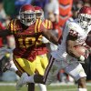 Oklahoma running back Brennan Clay, right, runs from Iowa State defensive back Jacques Washington during an 18-yard touchdown run in the second half of an NCAA college football game, Saturday, Nov. 3, 2012, in Ames, Iowa. Oklahoma won 35-20. (AP Photo/Charlie Neibergall)