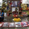Photo - A woman wipes photos of late President Hugo Chavez at a makeshift altar set in his honor at the main square of Sabaneta, western Venezuela on Saturday, March 9, 2013. Chavez, who died of cancer on March 5, 2013 was born in Sabaneta. His former home has been turned into the local headquarters of the United Socialist Party of Venezuela, PSUV. (AP Photo/Esteban Felix)