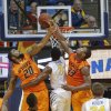 Photo - Oklahoma State's Marcus Smart (33) and Michael Cobbins (20) block the shot of West Virginia's Juwan Staten (3) during the second half of an NCAA college basketball game in Morgantown, W.Va., on Saturday, Feb. 23, 2013. Oklahoma State defeated West Virginia 73-57.(AP Photo/David Smith) ORG XMIT: WVDS114