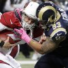 Arizona Cardinals quarterback Kevin Kolb, left, is sacked by St. Louis Rams defensive tackle Jermelle Cudjo during the third quarter of an NFL football game, Thursday, Oct. 4, 2012, in St. Louis. Cudjo was charged with an unnecessary roughness penalty on the play. (AP Photo/Seth Perlman)