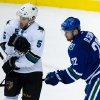 San Jose Sharks\' Jason Demers, left, is hit by a shot as Vancouver Canucks\' Daniel Sedin, of Sweden, watches during second period NHL hockey action in Vancouver, British Columbia, on Thursday Nov. 14, 2013. (AP Photo/The Canadian Press, Darryl Dyck)
