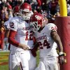 Photo -   Oklahoma running back Brennan Clay, right, celebrates with quarterback Landry Jones after scoring on an 18-yard touchdown run during the second half of an NCAA college football game against Iowa State, Saturday, Nov. 3, 2012, in Ames, Iowa. Oklahoma won 35-20. (AP Photo/Charlie Neibergall)