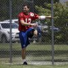 Photo - Indianapolis Colts quarterback Andrew Luck utilizes the fence as he stretches during practice at the NFL team's football training camp in Anderson, Ind., Sunday, July 28, 2013.  (AP Photo/Michael Conroy)