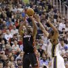 Miami Heat center Chris Bosh (1) shoots as Utah Jazz forward Derrick Favors, right, defends in the second quarter during an NBA basketball game Monday, Jan. 14, 2013, in Salt Lake City. (AP Photo/Rick Bowmer)