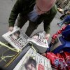 A man buys copies of newspapers in New York\'s Financial District featuring headlines of the death of Osama bin Laden, Monday, May 2, 2011. (AP Photo/Richard Drew)