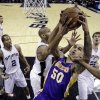 Los Angeles Lakers\' Robert Sacre (50) is blocked by San Antonio Spurs\' Tim Duncan, center, while trying to score during the first quarter of an NBA basketball game on Wednesday, Jan. 9, 2013, in San Antonio. (AP Photo/Eric Gay)