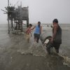 Residents carry their belongings towards their house on stilts as strong winds and rains caused by Typhoon Koppu hits the coastal town of Navotas, north of Manila, Philippines on Sunday, Oct. 18, 2015. Slow-moving Typhoon Koppu blew ashore with fierce wind in the northeastern Philippines early Sunday, toppling trees and knocking out power and communications. (AP Photo/Aaron Favila)