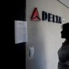 Photo - A woman reads a notice on the door of a closed Delta Airlines office in Caracas, Venezuela, Friday, Jan. 24, 2014. American Airlines, United and Panama's Copa Airlines were also among carriers whose offices were either closed or had halted sales on Friday after the government devalued the local currency, the Bolivar, for flights abroad.  (AP Photo/Alejandro Cegarra)