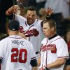 Atlanta Braves\' Chipper Jones, right, celebrates with Martin Pardo and Eric Hinske (20) after hitting a game-winning, two-run home run in the 10th inning of a baseball game against the Philadelphia Phillies in Atlanta, Wednesday, May 2, 2012. Atlanta won 15-13. (AP Photo/John Bazemore)