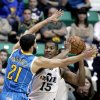 Photo - Utah Jazz's Derrick Favors (15) passes the ball against New Orleans Hornets' Greivis Vasquez (21), of Venezuela, in the first quarter during an NBA basketball game Wednesday, Jan. 30, 2013, in Salt Lake City. (AP Photo/Rick Bowmer)