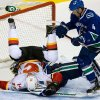 Calgary Flames\' Blake Comeau, left, crashes into Vancouver Canucks goalie Cory Schneider as Canucks\' Keith Ballard, right, watches during the second period an NHL hockey game game in Vancouver, British Columbia, on Wednesday, Jan. 23, 2013. (AP Photo/The Canadian Press, Darryl Dyck)