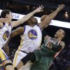 Photo - Milwaukee Bucks' Monta Ellis, right, has his shot blocked by Golden State Warriors' Carl Landry (7) and Klay Thompson (11) during the first half of an NBA basketball game Saturday, March 9, 2013, in Oakland, Calif. (AP Photo/Ben Margot)
