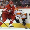 Photo - Carolina Hurricanes' Patrick Dwyer (39) checks Philadelphia Flyers' Michael Raffl (12), of Austria, during the first period of an NHL hockey game in Raleigh, N.C., Tuesday, Nov. 5, 2013. (AP Photo/Gerry Broome)