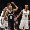 San Antonio Spurs\' Tony Parker (9) and Brooklyn Nets\' Keith Bogans (10) react after Parker scored in the first half of an NBA basketball game, Sunday, Feb. 10, 2013, at Barclays Center in New York. (AP Photo/Kathy Kmonicek)