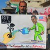 Photo - In this citizen journalism image provided by Edlib News Network, ENN, which has been authenticated based on its contents and other AP reporting, a protester holds a placard depicting U.S. President Barack Obama during a demonstration in Kafr Nabil town, Idlib province, northern Syria, Friday, Jan. 10, 2014. Rebel-on-rebel fighting between an al-Qaida-linked group and an array of more moderate and ultraconservative Islamists has killed nearly 500 people over the past week in northern Syria, an activist group said Friday, in the most serious bout of violence among opponents of Syrian President Bashar Assad since the civil war began. The Arabic on the poster is an acronym meaning,