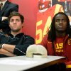 Photo - FILE - In this Dec. 3, 2013, file photo, Southern California quarterback Cody Kessler, left, and Josh Shaw watch a news conference for USC's new football coach Steve Sarkisian in Los Angeles. Shaw has admitted to lying to school officials about how he sprained his ankles last weekend, retracting his story about jumping off a balcony to save his drowning nephew. Shaw has been suspended indefinitely from all of the Trojans' team activities after acknowledging his heroic tale was