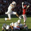 Oklahoma State\'s Clint Chelf (10) leaps over teammates Lane Taylor (68) and Parker Graham (71) after catching a pass as Oklahoma\'s Aaron Colvin (14) reacts in the second quarter during the Bedlam college football game between the University of Oklahoma Sooners (OU) and the Oklahoma State University Cowboys (OSU) at Gaylord Family-Oklahoma Memorial Stadium in Norman, Okla., Saturday, Nov. 24, 2012. Photo by Nate Billings , The Oklahoman