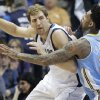 Photo - Dallas Mavericks forward Dirk Nowitzki (41) of Germany keeps the ball from Denver Nuggets forward Wilson Chandler (21) during the first half an NBA basketball game Friday, March 21, 2014, in Dallas. (AP Photo/LM Otero)