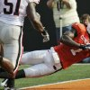 FILE - OSU: In this Sept. 5, 2009, file photo, Oklahoma State University\'s Dez Bryant dives into the end zone for a touchdown against Georgia during the fourth quarter of an NCAA college football game in Stillwater, Okla. (AP Photo/Sue Ogrocki, File) ORG XMIT: NY176