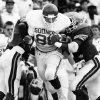 University of Oklahoma tight end Keith Jackson carries two Tulsa defenders for extra yardage to set up OU\'s fourth touchdown of the game late in the second quarter. The Sooners downed the Tulsa Hurricane 65-0 in Tulsa. Staff photo by Paul Hellstern taken 9/26/87.