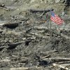 Workers carrying hand tools and shovels walk past a U.S. flag, Tuesday, April 1, 2014, near Darrington, Wash., in the debris field of the deadly mudslide that hit the community of Oso,Wash. on March 22, 2014. (AP Photo/Ted S. Warren)