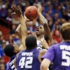 Kansas guard Andrew Wiggins, back, shoots over Kansas State defenders Wesley Iwundu, left, Thomas Gipson (42) and Will Spradling (55) during the first half of an NCAA college basketball game in Lawrence, Kan., Saturday, Jan. 11, 2014. (AP Photo/Orlin Wagner)