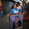 Photo - A woman holds a painting of President Hugo Chavez as supporters gather around Bolivar square after his return to the country in Caracas, Venezuela, Monday, Feb. 18, 2013.  Chavez returned to Venezuela early Monday after more than two months of medical treatment in Cuba following cancer surgery. The government didn't offer an explanation as to why Chavez made his surprise return while he is undergoing other treatments that have not been specified.(AP Photo/Fernando Llano)