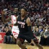 Miami Heat guard Mario Chalmers (15) drives past Houston Rockets guard Pat Beverley during the first quarter of an NBA basketball game, Tuesday, March, 4, 2014, in Houston. (AP Photo/Patric Schneider)