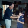 """ADVANCE FOR USE SUNDAY, APRIL 28, 2013 AND THEREAFTER - In this circa 1997 photo provided by the family, Timothy O\'Brien adjusts the Cub Scout uniform of his son, Ian, at their home in Santee, Calif. In early 2013, Ian O\'Brien, 23, wrote an opinion piece tied to the Boy Scout debate and his own experience in the Scouts when he was growing up in the San Diego area. """"To put it simply: Being a boy is supposed to look one way, and you get punished when it doesn\'t,"""" O\'Brien wrote in the piece, which appeared in The Advocate, a national magazine for the gay, lesbian, bisexual and transgender communities. (AP Photo/Ian O\'Brien)"""