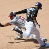 Photo - Minnesota Twins first baseman Kendrys Morales, back, fields a throw to put out Colorado Rockies Carlos Gonzalez at first base after a dropped third strike in the fourth inning of an interleague baseball game in Denver on Sunday, July 13, 2014. (AP Photo/David Zalubowski)
