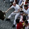 A reveler grabs the horn of an Alcurrucen\'s ranch fighting bull during the running of the bulls of the San Fermin festival, in Pamplona, Spain, Sunday, July 7, 2013. Revelers from around the world arrive to Pamplona every year to take part on some of the eight days of the running of the bulls glorified by Ernest Hemingway\'s 1926 novel