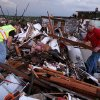 Volunteer firefighters William Jackson, left, and Ashley Martin, center, from Oklahoma, and Johnny Ward of Joplin look through the wreckage of a home where it was feared a pregnant woman as feared to be trapped following a tornado in Joplin, Mo., Sunday, May 22, 2011. A large tornado moved through much of the city, damaging a hospital and hundreds of homes and businesses. The three did not find anyone during their search. (AP Photo/Mark Schiefelbein) ORG XMIT: MOMS110