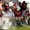 Photo - Head coach Bob Stoops, center, OU President David L. Boren (white shirt) and other coaches take the ice bucket challenge during the University of Oklahoma Sooners (OU) practice and Student Day at Gaylord Family-Oklahoma Memorial Stadium in Norman, Okla., on Thursday, Aug. 21, 2014. Photo by Steve Sisney, The Oklahoman